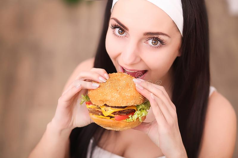 Young woman in a fine dining restaurant eat a hamburger, she behaves improperly.  royalty free stock photography