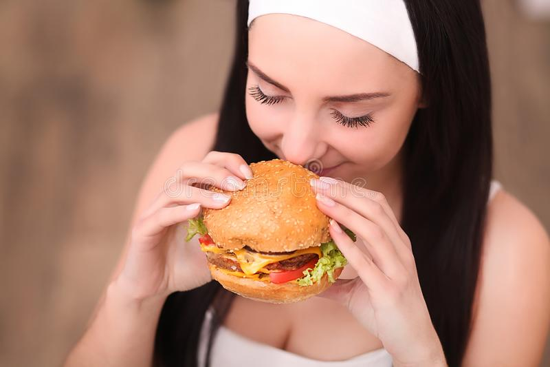 Young woman in a fine dining restaurant eat a hamburger, she behaves improperly. A young woman holding a burger in a measuring tape. A girl stands on a wooden royalty free stock photo