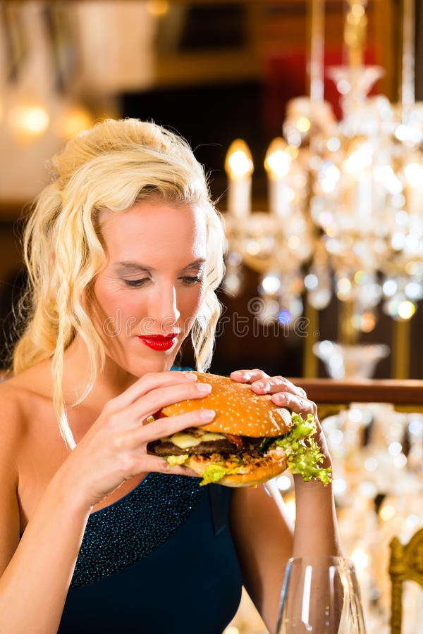 Young woman in fine restaurant, she eats a burger. Young woman in a fine dining restaurant eat a hamburger, she behaves improperly stock image