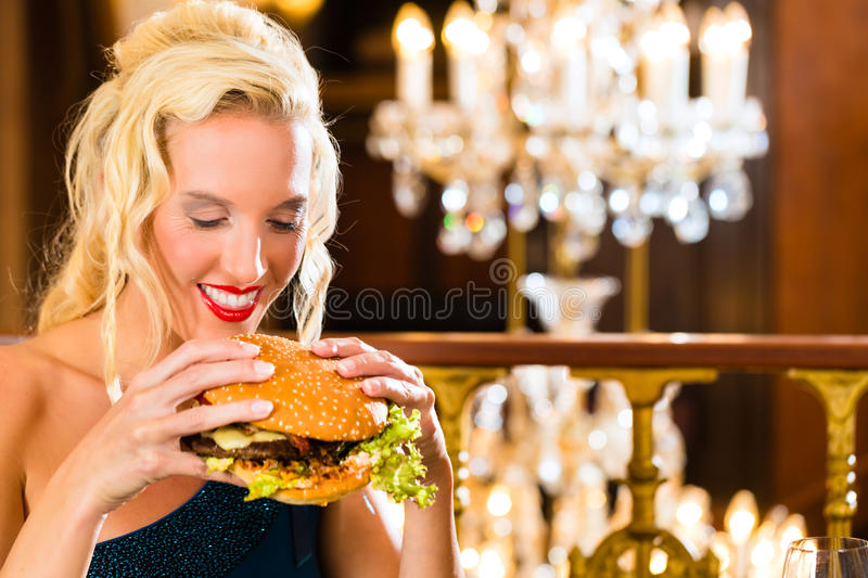 Young woman in fine restaurant, she eats a burger. Young woman in a fine dining restaurant eat a hamburger, she behaves improperly royalty free stock images