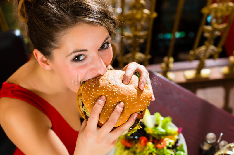 Young woman in fine restaurant, she eats a burger. Young woman in a fine dining restaurant eat a hamburger, she behaves improperly stock photography