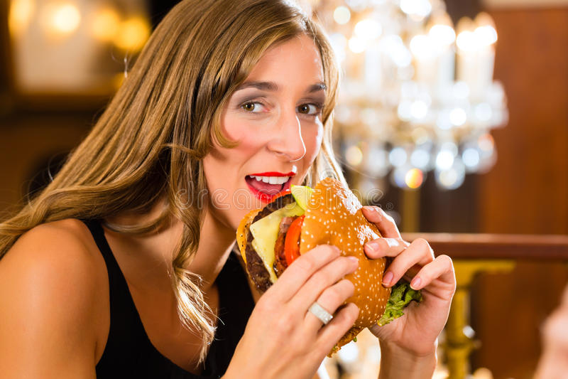 Young woman in fine restaurant, she eats a burger. Young woman in a fine dining restaurant eat a hamburger, she behaves improperly royalty free stock photos