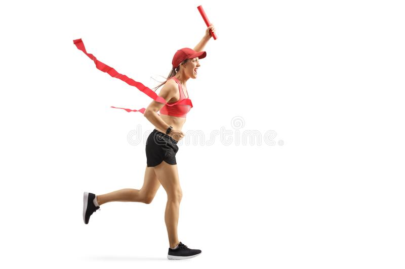 Young woman on the finish line of relay race carrying a baton royalty free stock photos