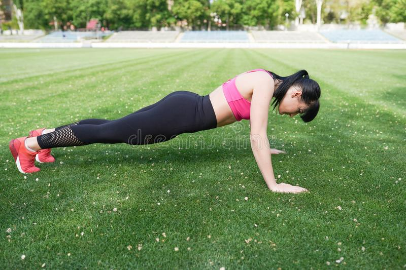 Young woman with fit body on green background. Female model in sportswear exercising outdoors royalty free stock photo