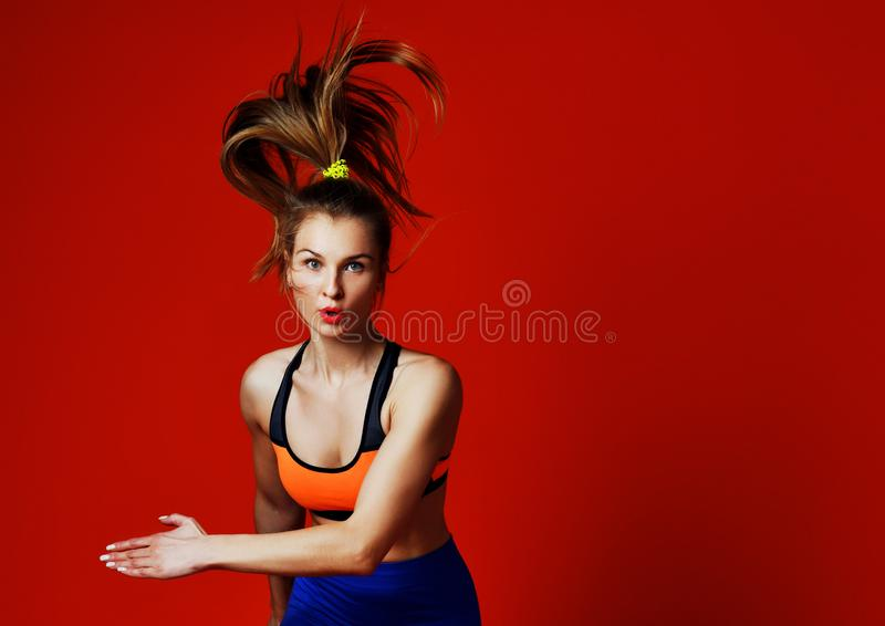 Young woman with fit body jumping and running against grey background. stock photo
