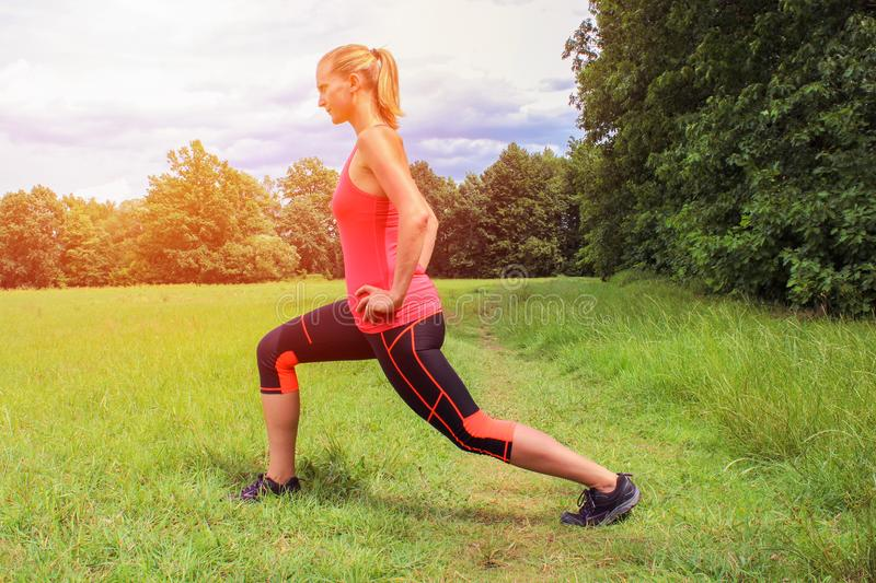 Young woman in fitness exercise lunge with strong light. stock photos