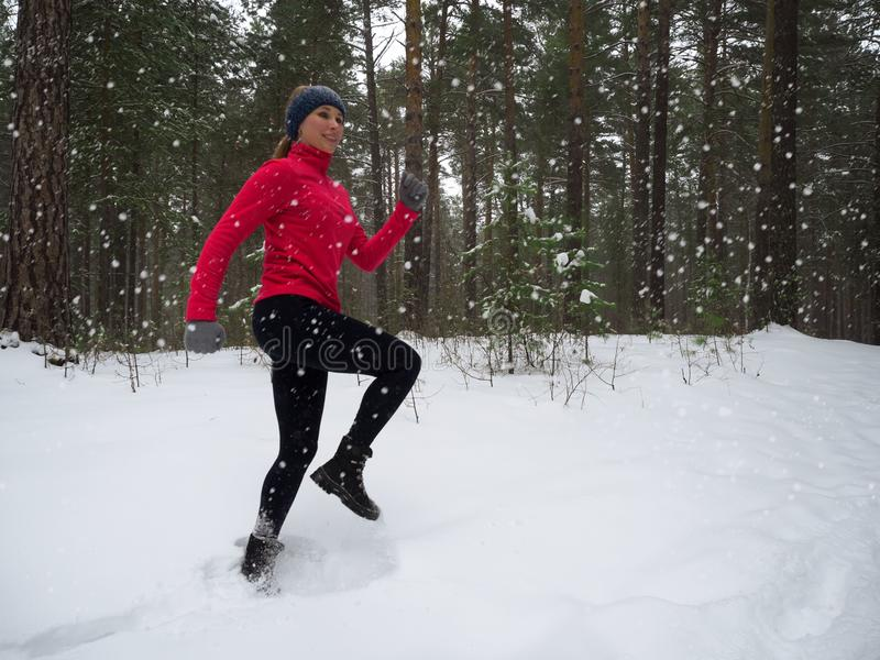 Young woman fitness model running in a city park. Winter running exercise. royalty free stock image