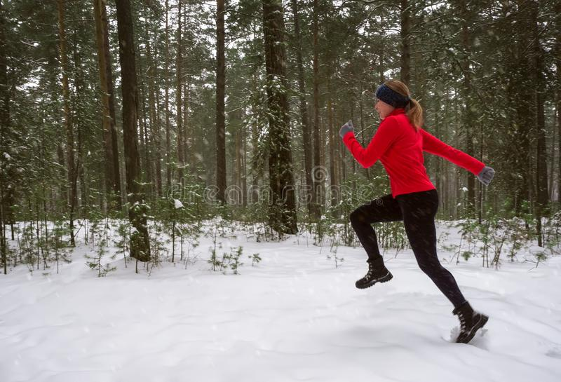 Young woman fitness model running in a city park. Winter running exercise. royalty free stock photography