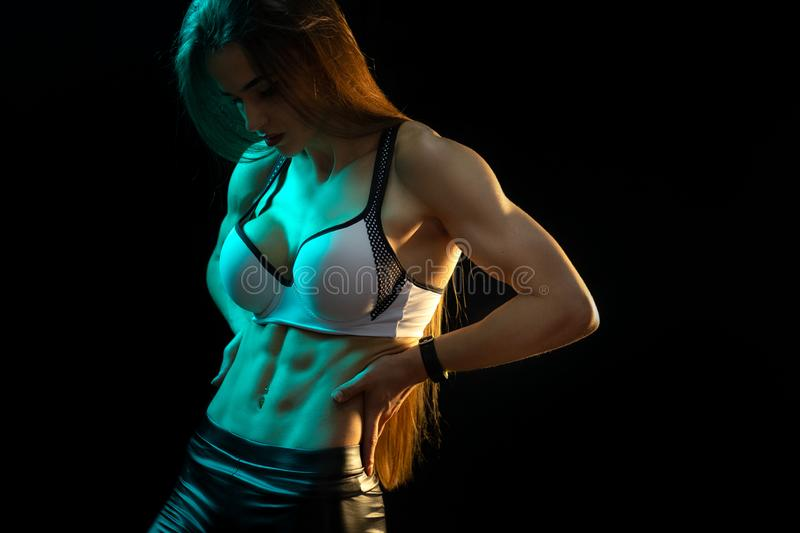 Young woman fitness model showing her perfect abs in neon lights silhouette in the studio. Young woman fitness model showing her perfect abs in neon lights royalty free stock images