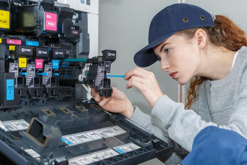 Young woman fixing printer. Young woman fixing a printer royalty free stock photography