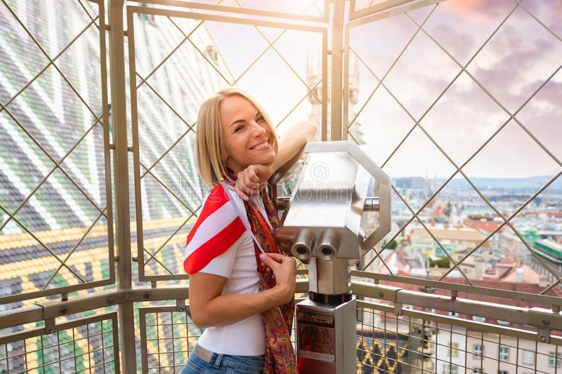A young woman with the flag of Austria in her hands looks through observation binoculars and enjoys the panorama of the royalty free stock photos