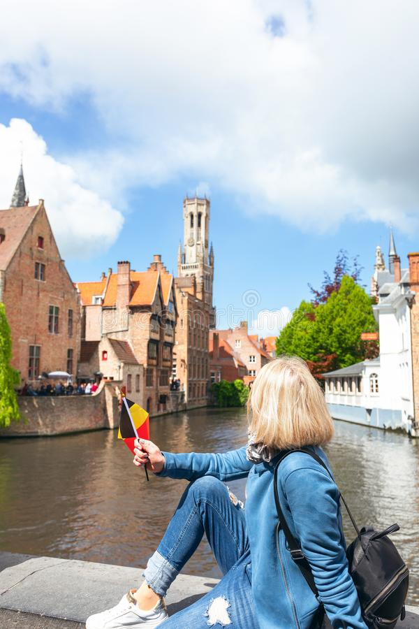 A young woman with the flag of Belgium in her hands is enjoying the view of the canals in the historical center of stock photography