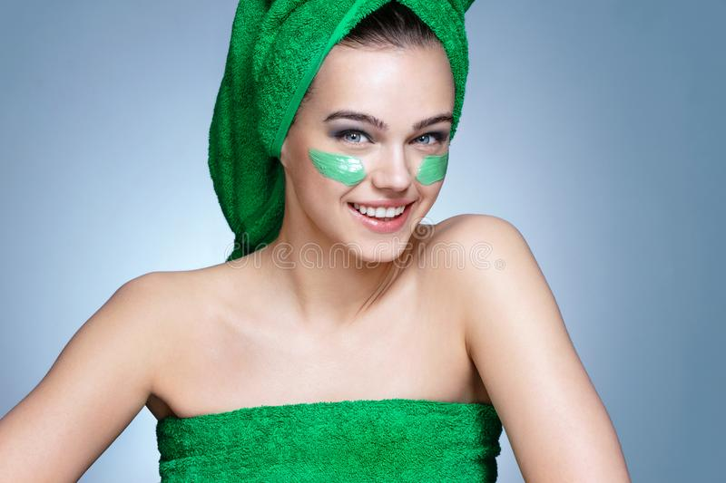 Young woman with flawless skin, applying moisturizing cream on her face stock images