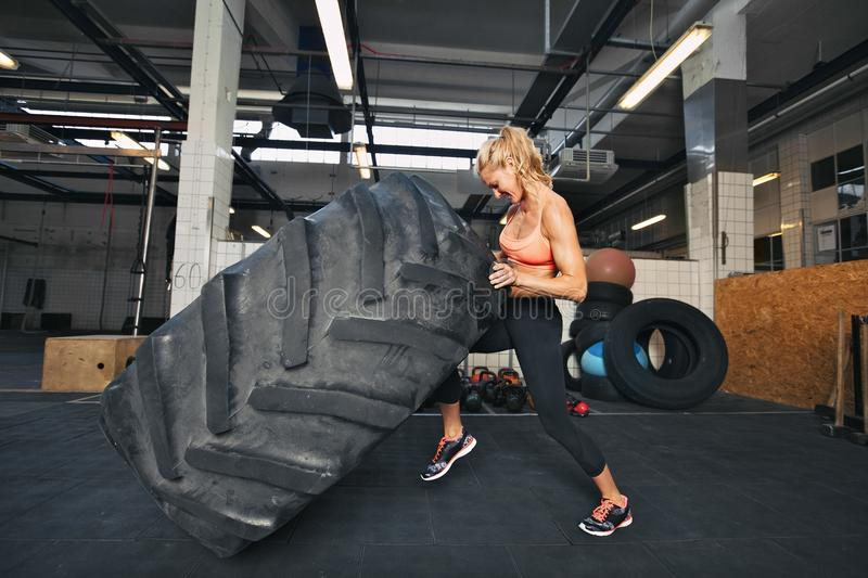 Young woman flipping tire at gym stock images