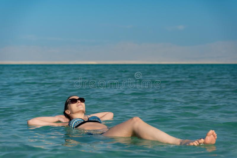 Young woman floating on the water surface of the dead sea. Woman taking a tan and relaxing in the dead sea. holiday concept royalty free stock photo