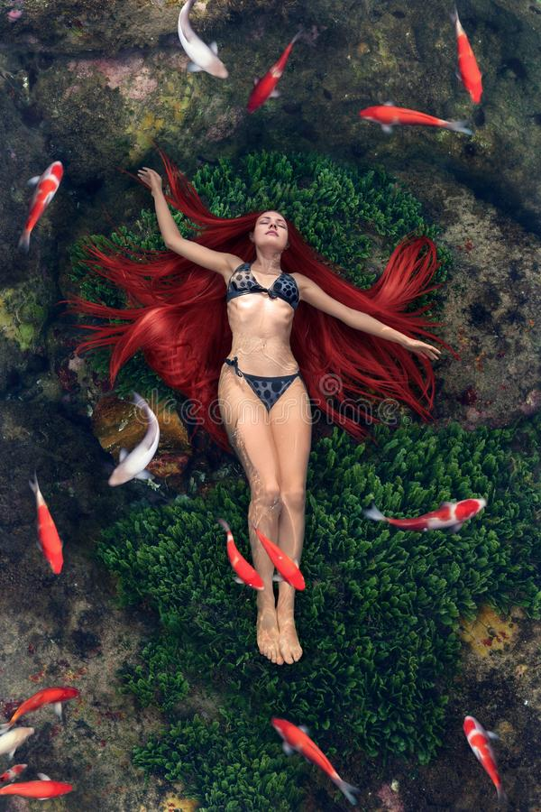 Young woman floating in water stock photos