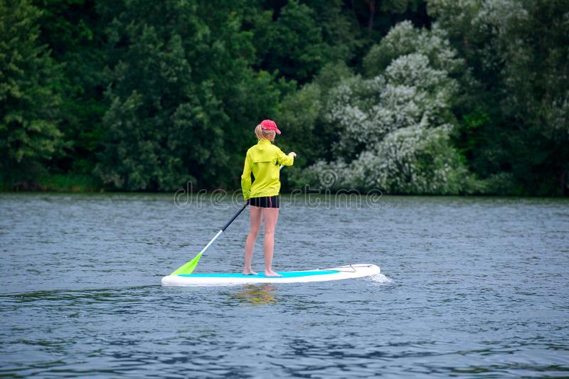 A young woman floats on a SUP board along a large river. Swim on the board for amazing outdoor activities. The young woman floats on a SUP board along a large stock photography