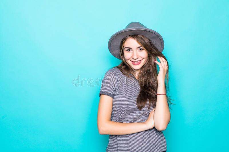 Young woman in floppy hat posing. Portrait of girl with long hair, in gray floppy hat, posing isolated on blue background. Young woman in floppy hat posing stock photos