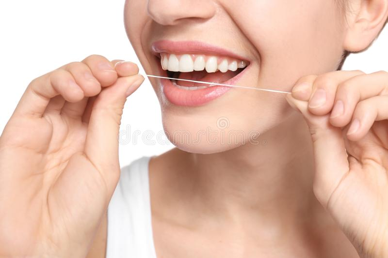 Young woman flossing her teeth on white background. Closeup royalty free stock image