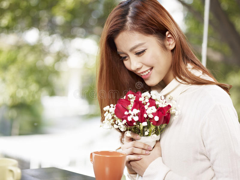 Young woman with flowers. Young asian woman in love holding flowers and smiling, valentine's day theme stock image