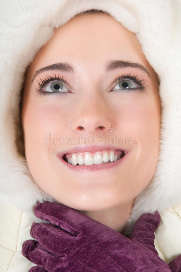 Young woman with fluffy hood, winter gloves. Headshot of beautiful young woman with white fluffy hood, purple winter gloves, smiling and looking up waiting for stock photography