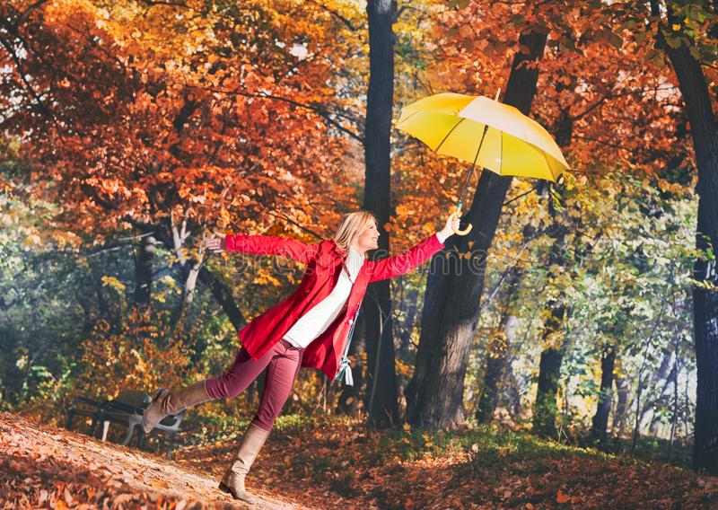Young woman flying in the autumn park with yellow umbrella royalty free stock photos
