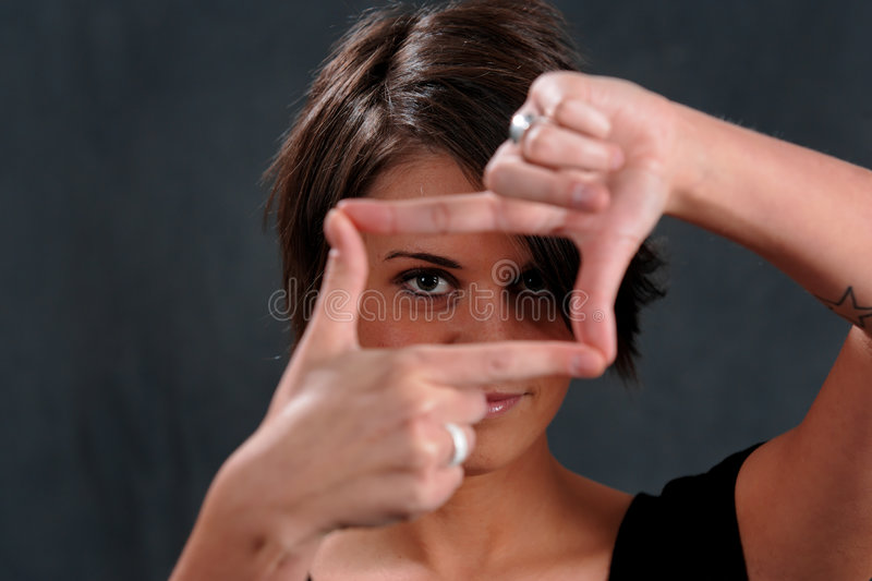 Young Woman Focus. Young Woman with hands in focus shape in front of face
