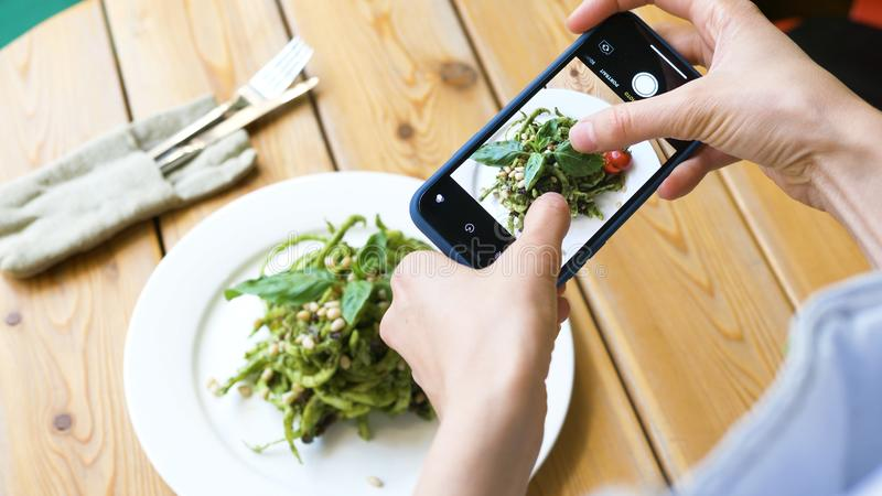 Young woman focuses camera on green salad and makes photo. Woman raw food fan focuses camera to green fresh salad on brown round wooden table and makes photo stock photos