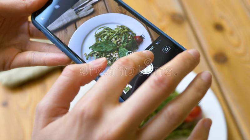 Young woman focuses camera on plate with green fresh salad stock photos