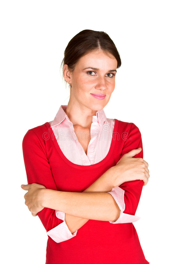 Young woman with folded arms. Beautiful young brunette woman standing with arms folded in front looking at the viewer. Image is isolated on a white background stock images