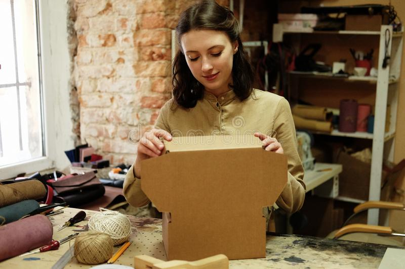 Young brunette woman folds packing box in sewing workshop. Young woman folds packing box in sewing workshop royalty free stock photo