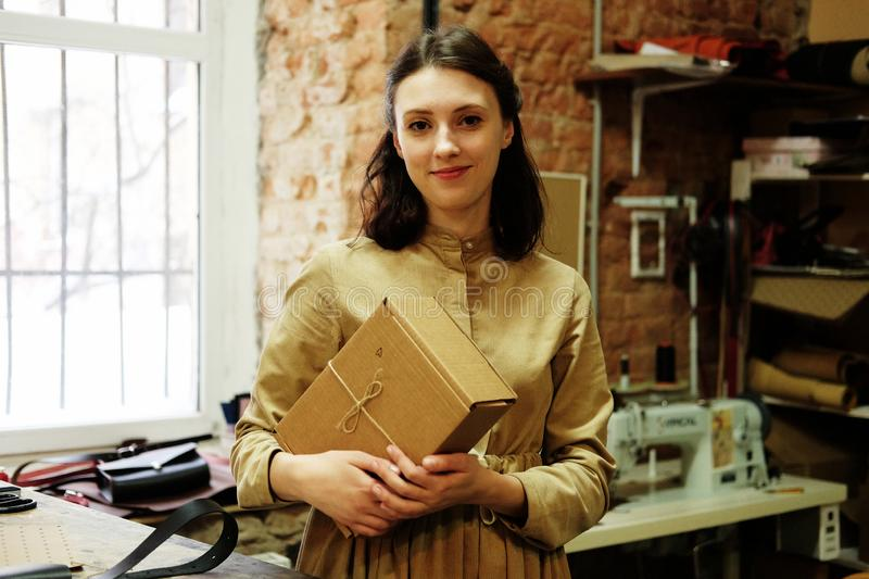 Young brunette woman folds packing box in sewing workshop. Young woman folds packing box in sewing workshop stock images