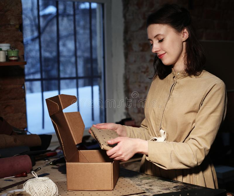 Young woman folds packing box in sewing workshop. Close up royalty free stock photo