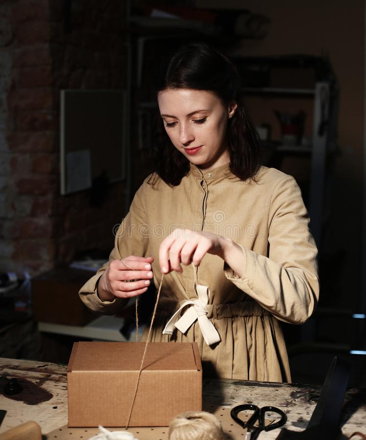Young woman folds packing box in sewing workshop. Close up royalty free stock photos