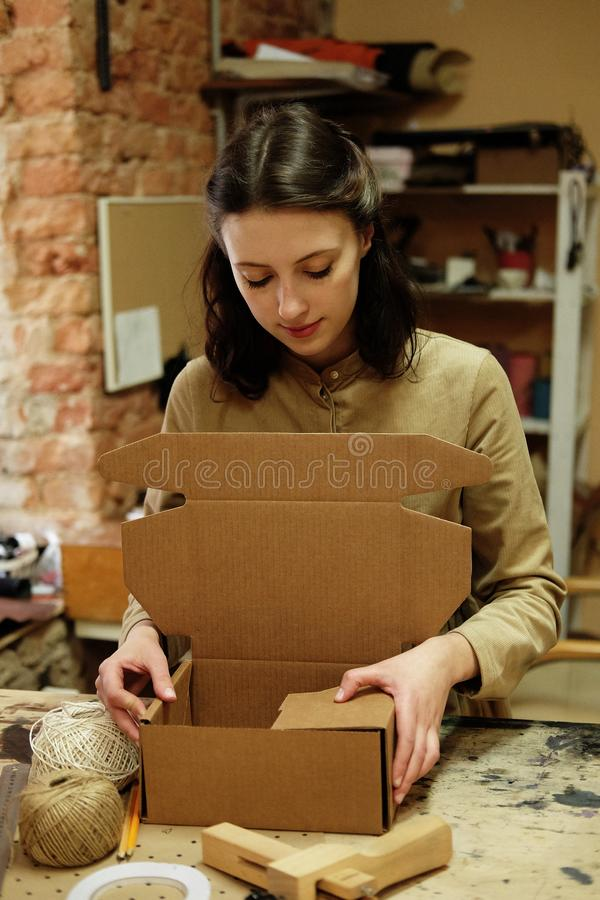 Young woman folds packing box in sewing workshop. Close up royalty free stock image