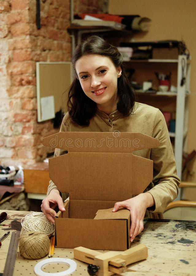 Young brunette woman folds packing box in sewing workshop. Young woman folds packing box in sewing workshop stock photo