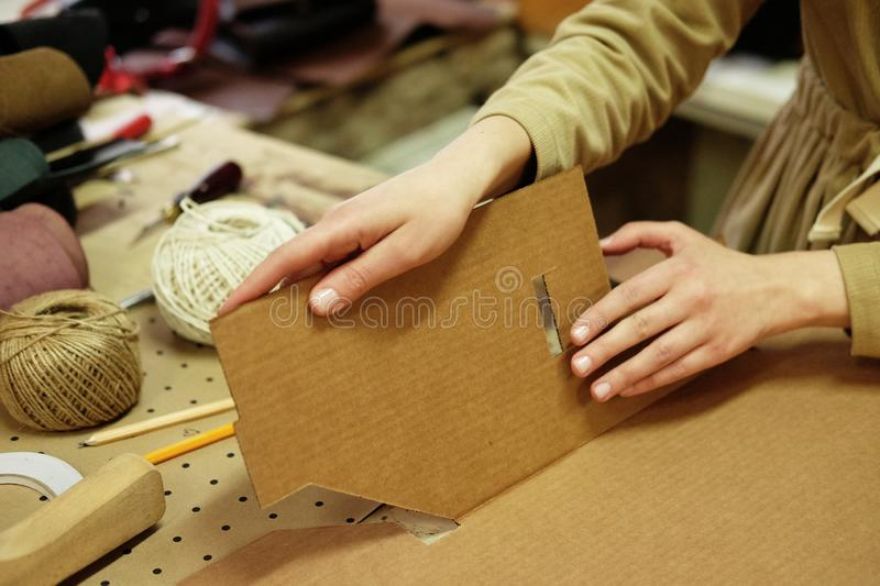 Young woman folds packing box in sewing workshop. Young happy woman folds packing box in sewing workshop royalty free stock photo