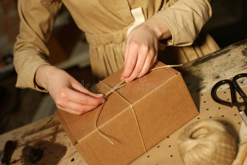 Young woman folds packing box in sewing workshop. Close up stock image