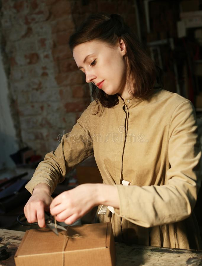 Young woman folds packing box in sewing workshop. Close up royalty free stock photography