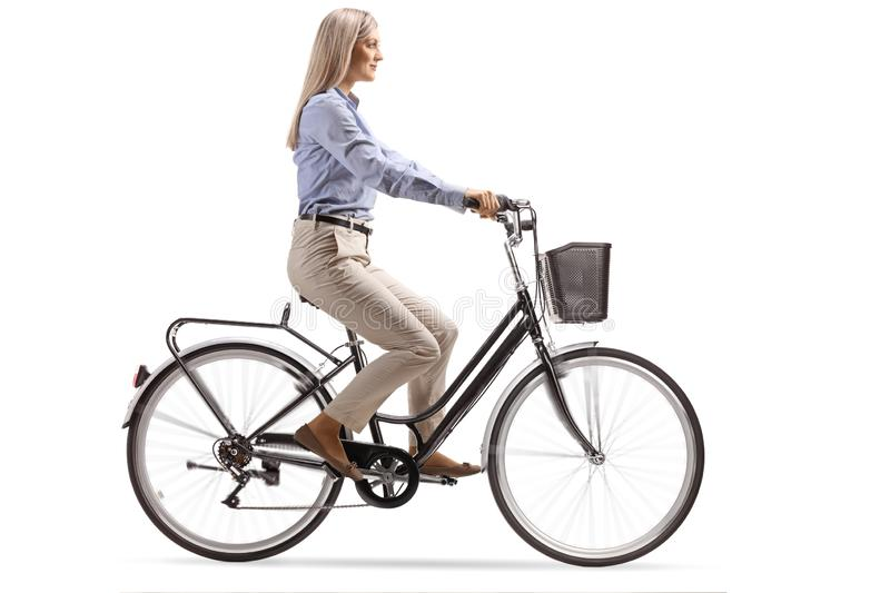 Young woman in formal clothes riding a bicycle. Isolated on white background royalty free stock photo