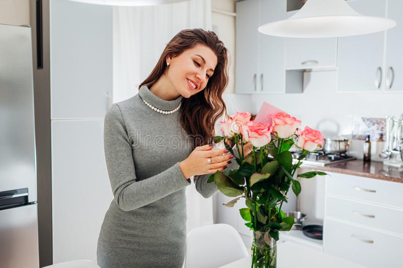 Young woman found bouquet of roses with card on kitchen. Happy girl reading note in flowers. Valentines day stock photos