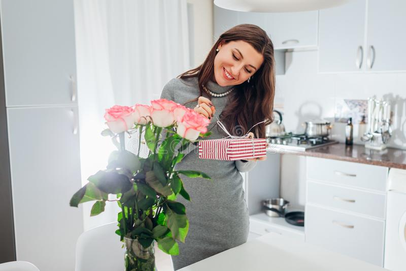 Young woman found gift box and bouquet of roses on kitchen. Happy smiling girl opening present. For Valentines day stock photo