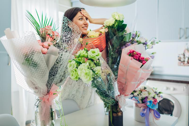 Young woman found many bouquets of flowers on kitchen. Happy excited girl smiling royalty free stock image