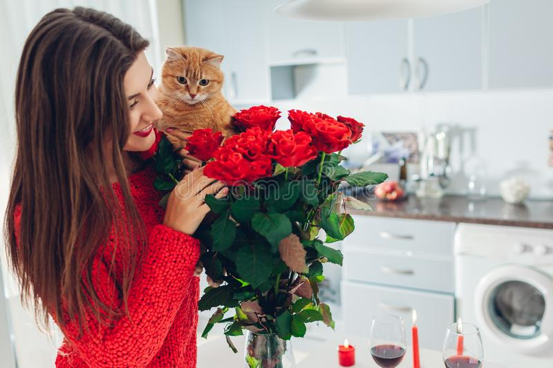 Young woman found red roses with candle, wine and gift box on kitchen. Happy girl smelling flowers with cat. Women`s day royalty free stock images