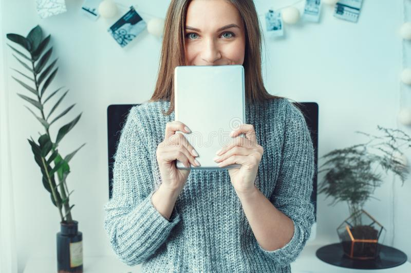 Young woman freelancer indoors home office concept casual style holding digital tablet. Young female freelancer at home office casual standing cover face with royalty free stock photos