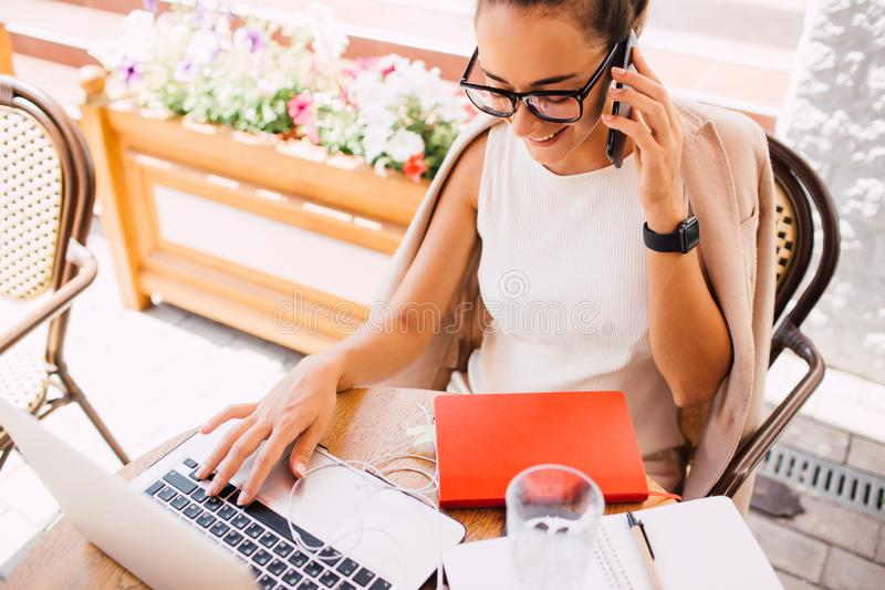 Young woman freelancer using laptop and smartphone in street cafe royalty free stock photo