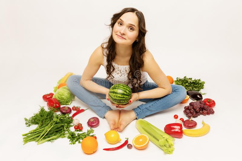Young woman with fresh various vegetables and fruits royalty free stock photography