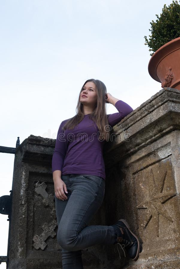 Woman in front of antique fence. Young woman in front of antique fence in Frascati, Italy, looks serious stock photo