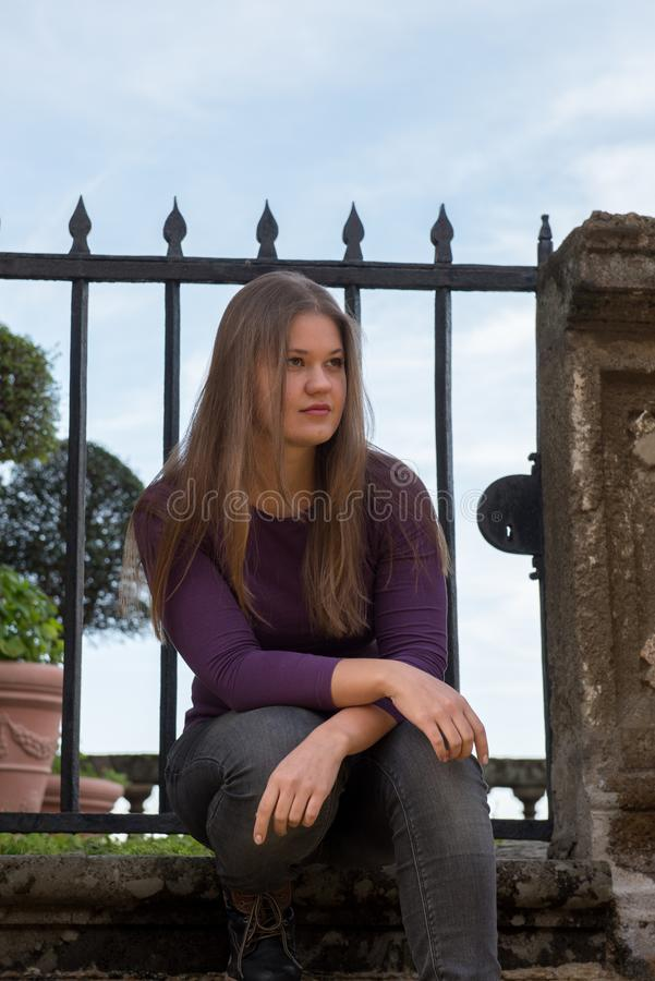 Woman in front of antique fence. Young woman in front of antique fence in Frascati, Italy, looks serious stock photos