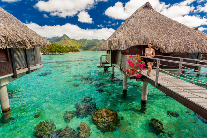 Young woman in front of luxury over water bungallows. In tropical resort stock image